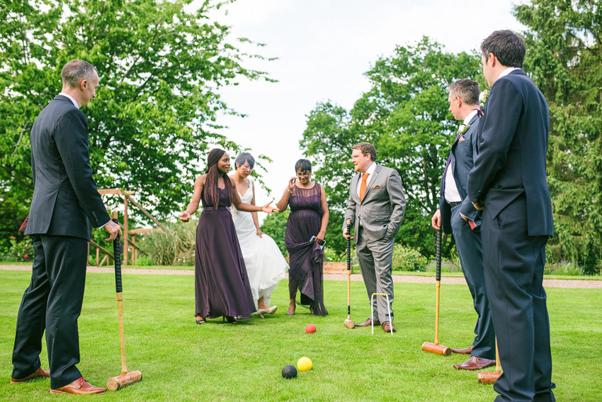 bride and groom parties play croquet